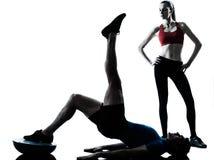 Coach man woman exercising abdominals with bosu stock photos