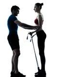 Coach man woman exercising gymstick Stock Photos