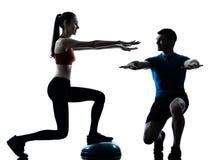Coach man woman exercising squats on bosu. Personal trainer men coach and women exercising squats on bosu silhouette  studio isolated on white background Royalty Free Stock Photo