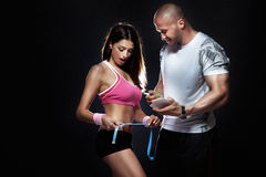Coach measured body of attractive brunette girl. Photo of attractive couple at the gym. Coach measured body of beautiful brunette women with perfect fitness Royalty Free Stock Photography