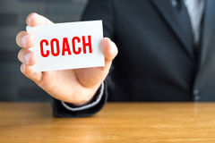 Coach, message on white card and hold by Stock Images