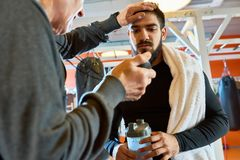 Coach Motivating Sportsman at Practice. Portrait of coach motivating bearded Middle-Eastern  fighter at practice in martial arts club, copy space Stock Images