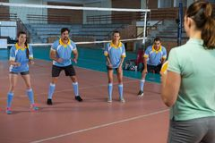 Coach playing volleyball with players Stock Photo
