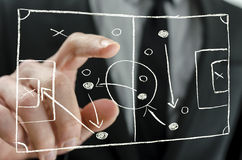 Coach pointing to a football strategy plan. Closeup of coach pointing to a football strategy plan drawn on a virtual screen stock photos