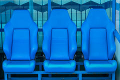 Coach and reserves blue bench on a football stadium Royalty Free Stock Photos