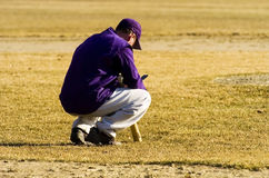 Coach's Call. A baseball coach or player croutches on the infield checking his wireless cell phone Royalty Free Stock Photo