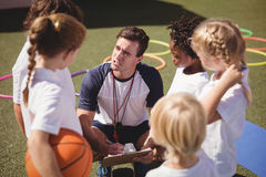 Coach and schoolkids discussing on clipboard. In schoolyard Royalty Free Stock Photography