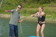 Coach showing something to water ski performer. Male Stock Photo