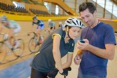 Coach showing timer to cyclist. Coach Stock Photos
