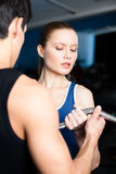 Coach shows woman the correct exercise performing Royalty Free Stock Photos