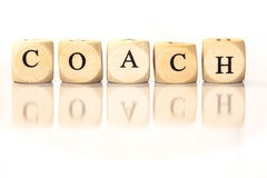Coach spelled word, dice letters with reflection Stock Photo