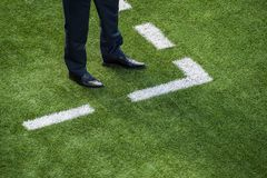 Coach standing next to chalk line on soccer field royalty free stock photos