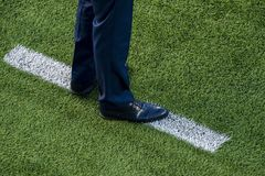 Coach standing next to chalk line on soccer field stock image