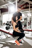 Coach straightens the back of the girl who sits on the bench in the gym.  stock photography