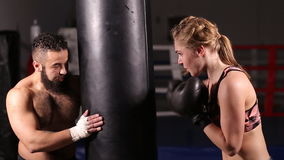 Coach with a student in boxing training. Girl in boxing gloves is working out a blow on the punching pear stock video