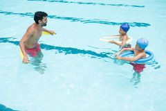 Coach and students interacting with each other in swimming pool Royalty Free Stock Image