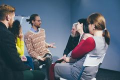 Coach and support group during psychological therapy. Group therapy.Patients comfort each other during psychological session. Toned concept royalty free stock photography