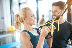 Coach talking with blonde fitness woman training with trx fitness straps Stock Photo