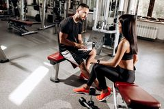 Coach talks with athletic girl dressed in black sport clothes sitting on the bench in the gym royalty free stock images