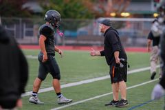 A Coach Talks To One Of His High School Football Players. A coach advises one of his high school football players stock photo