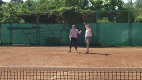 Coach girl teaches tennis player to hold racket and serve. Coach teaches tennis player to hold racket and serve stock video