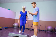 Coach timing elderly woman on doing stepper. Coach timing the elderly women on doing the stepper stock photos