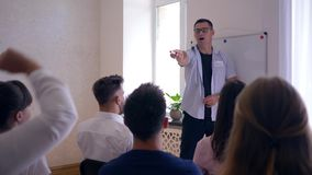 Coach training, team leader presents new business plan on whiteboard for active colleagues in room stock video footage