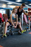 Coach watches sexy girl exercising on simulator Stock Photo