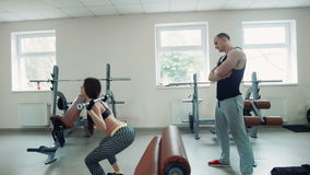 Coach watching sportswoman doing squats with bar. Sportswoman doing squats while trainer watching her technique stock footage