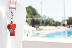 Coach whistle near swimming pool. Living coral theme - color of the year 2019. Coach whistle near outdoor swimming pool Horizontal. Living coral theme - color of stock photo