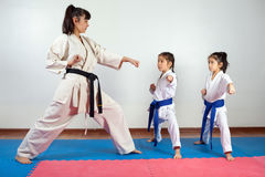 Coach woman showing martial art for children. Coach women showing martial art for children. Fighting position, active lifestyle, expressing emotions stock photo