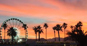 Coachella valley. Coachella at sunset with palm trees and the Ferris wheel in the background s Stock Photos