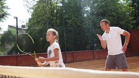 Coacher, das junges Mädchen zum Spielen von Tennis unterrichtet stock video