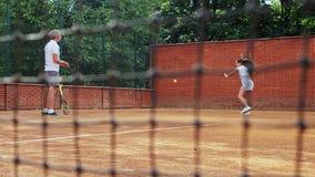 Coacher die jong meisje onderwijzen aan het spelen van tennis stock videobeelden