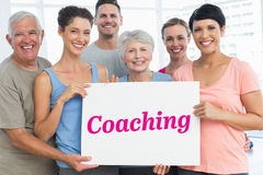 Coaching against grey wall. The word coaching and fit people holding blank board in yoga class against grey wall Stock Photos