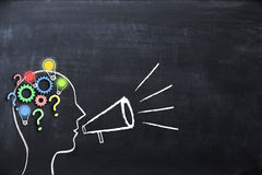 Coaching concept – knowledge and ideas sharing with human head shape and megaphone or bullhorn on blackboard. Coaching concept – knowledge sharing with stock photos