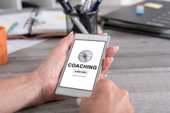 Coaching concept on a smartphone. Female hand holding a smartphone with coaching concept Royalty Free Stock Photography