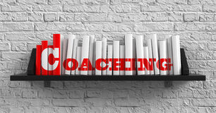 Coaching. Education Concept. Coaching - Red Inscription on the Books on Shelf on the White Brick Wall Background. Education Concept Royalty Free Stock Photo