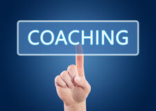 Coaching. Hand pressing Coaching button on interface with blue background royalty free stock photos