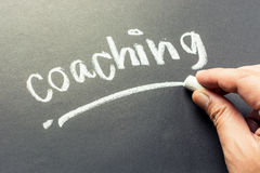 Coaching. Hand writing Coaching topic on chalkboard Stock Images