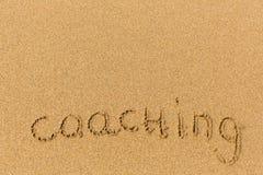 Coaching - inscription on sand beach. Background. Stock Photos
