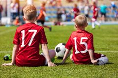 Coaching Kids Soccer. Young Boys Sitting on Football Field. Football Match for Children. Coaching Kids Soccer. Young Boys Sitting on Football Field and Watching Royalty Free Stock Photos