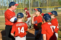 Coaching Little League Baseball. A coach gving last minute directions to his team before a game Royalty Free Stock Image
