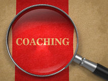 Coaching - Magnifying Glass Concept. Coaching Concept. Magnifying Glass on Old Paper with Red Vertical Line Background Royalty Free Stock Photos