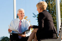 Coaching outdoors. A men and a women have a coaching discussion Stock Image