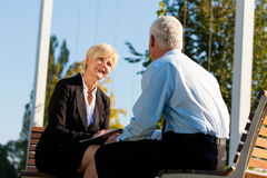Coaching outdoors. A men and a women have a coaching discussion Stock Photo