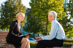 Coaching outdoors. A men and a women have a coaching discussion Royalty Free Stock Photos