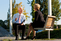 Coaching outdoors. A men and a women have a coaching discussion Royalty Free Stock Images