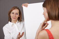Coaching talk. Women holding a blank board talking to a customer royalty free stock photos