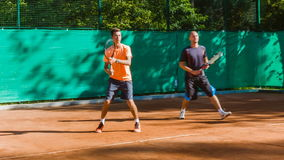 Coaching or teaching play tennis on a court outdoor. Training of professional sports players stock video